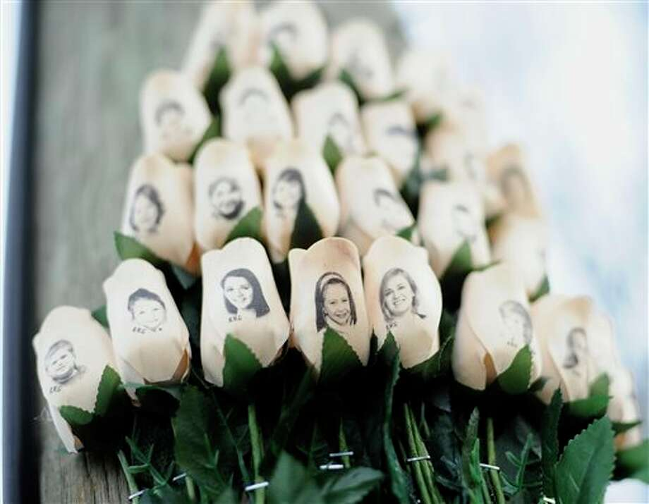 FILE - In this Jan. 14, 2013 file photo, white roses with the faces of victims of the Sandy Hook Elementary School shooting are attached to a telephone pole near the school on the one-month anniversary of the shooting that left 26 dead in Newtown, Conn. Some Newtown families have said they were given a voice late in the process of dispersing the millions of dollars in donated funds, and that the process has been bureaucratic, difficult, unpleasant, and has added to their pain. (AP Photo/Jessica Hill, File) / FR125654 AP