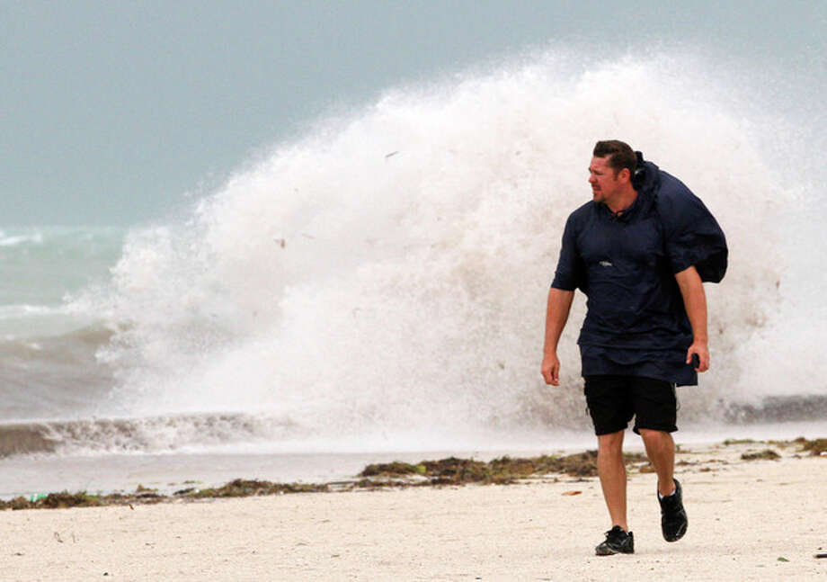 A man walks on the beach in Key West, Fla., Sunday, Aug. 26, 2012 as heavy winds hit the northern coast from Tropical Storm Isaac. Isaac is expected to continue streaming across Marion County Monday as it continues toward the northern Gulf of Mexico. National Weather Service officials in Jacksonville on Sunday said Marion County began getting rain bands from Isaac around 2 p.m. and that the rain would continue through Tuesday. (AP Photo/Alan Diaz) / AP