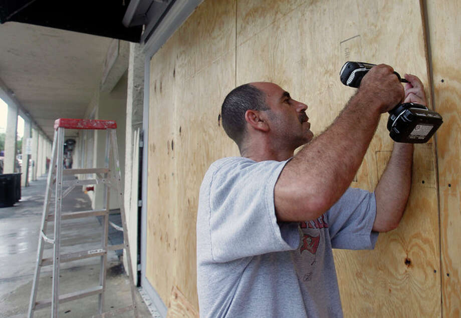 Oren Eshel boards a storefront on Duval Street in Key West, Fla., Saturday, Aug. 25, 2012 in preparation for Tropical Storm Isaac, Saturday, Aug. 25, 2012. Isaac's winds are expected to be felt in the Florida Keys by sunrise Sunday morning. (AP Photo/Alan Diaz) / AP