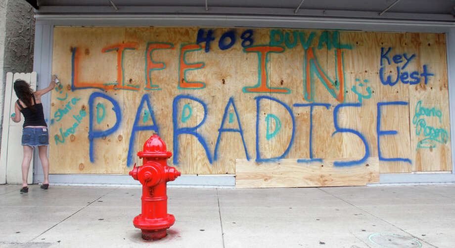 Shira Edllan Gervasi, of Israel, puts her name on plywood protecting a storefront in Key West, Fla., in anticipation of Tropical Storm Isaac on Saturday, Aug. 25, 2012. Isaac's winds are expected to be felt in the Florida Keys by sunrise Sunday morning. (AP Photo/Alan Diaz) / AP