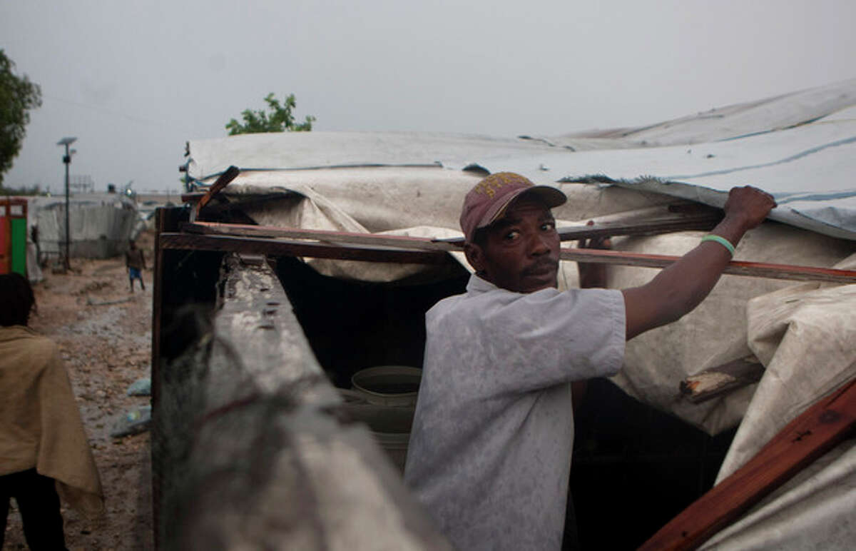 A man works to repair the roof of his tent in a camp for people displaced by the 2010 earthquake as Tropical Storm Isaac affects Port-au-Prince, Haiti, Saturday, Aug. 25, 2012. Tropical Storm Isaac swept across Haiti's southern peninsula early Saturday, dousing a capital city prone to flooding and adding to the misery of a poor nation still trying to recover from the 2010 earthquake. (AP Photo/Dieu Nalio Chery)