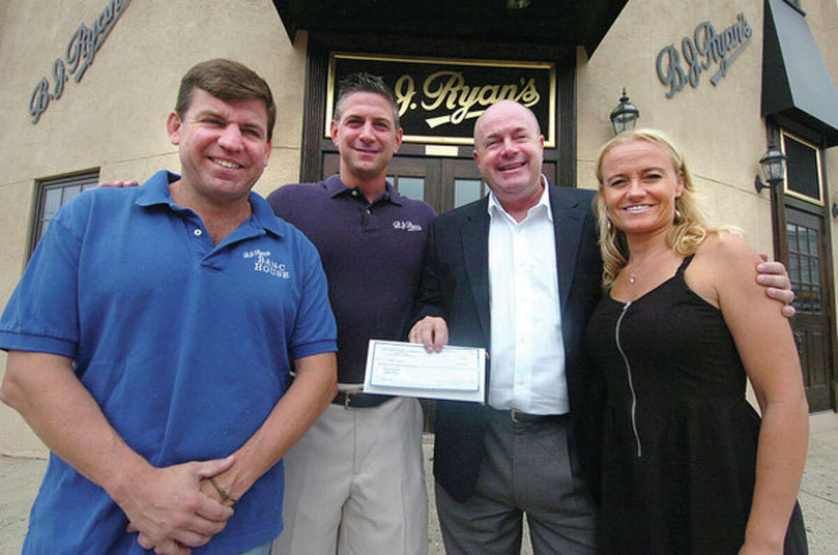 Hour Photo/ Alex von Kleydorff Left to right, co-owners Buckley Ryan and BJ Lawless are presented with a check from Reverend Shawn Moninger and Christina Connors for the BJ Ryan's Foundation. The Foundation will benefit the Norwalk Education Foundation and the Whittingham Cancer Center at Norwalk Hospital. The money was raised during the