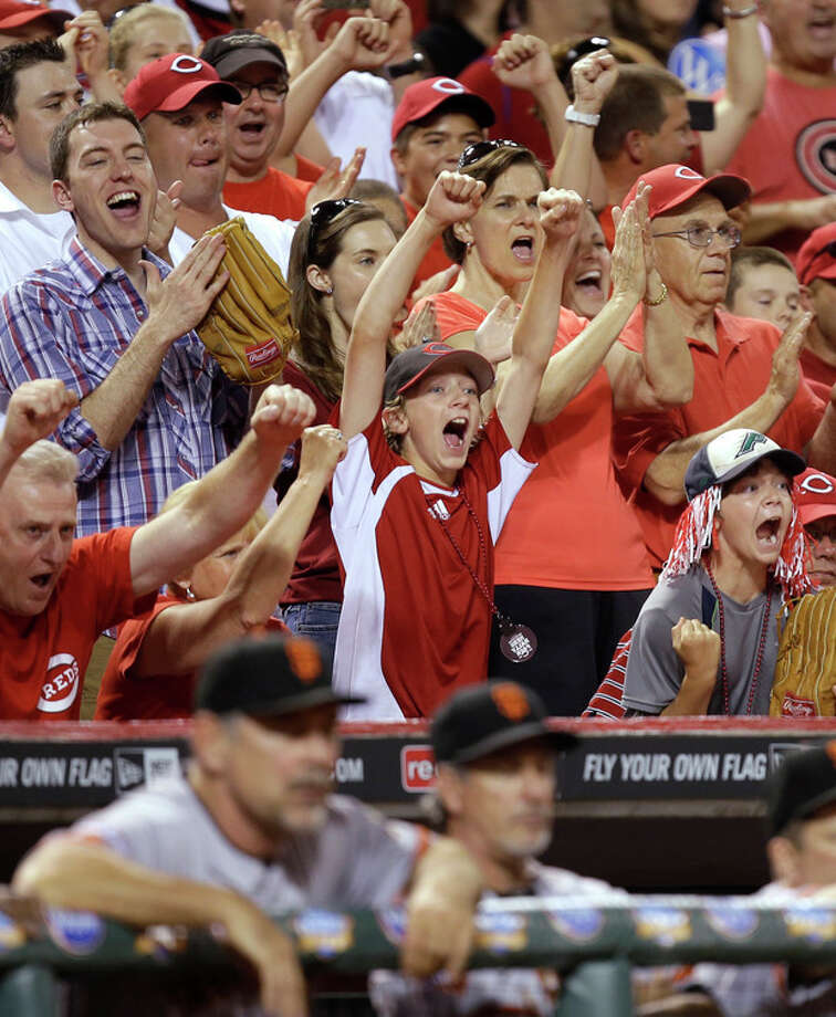 Cincinnati Reds fans celebrate behind the San Francisco Giants dugout with two outs in the ninth inning of a baseball game, Tuesday, July 2, 2013, in Cincinnati. Cincinnati won 3-0 on a no-hitter by Homer Bailey. (AP Photo/Al Behrman) / AP