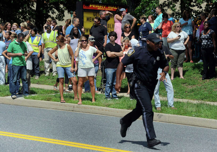 Parents wait to reunite with their children after a student was shot and critically wounded on the first day of classes at Perry Hall High School, Monday, Aug. 27, 2012, in Perry Hall, Md. A suspect was taken into custody shortly after the shooting, according to police. No one else was reported injured. (AP Photo/Steve Ruark) / FR96543 AP