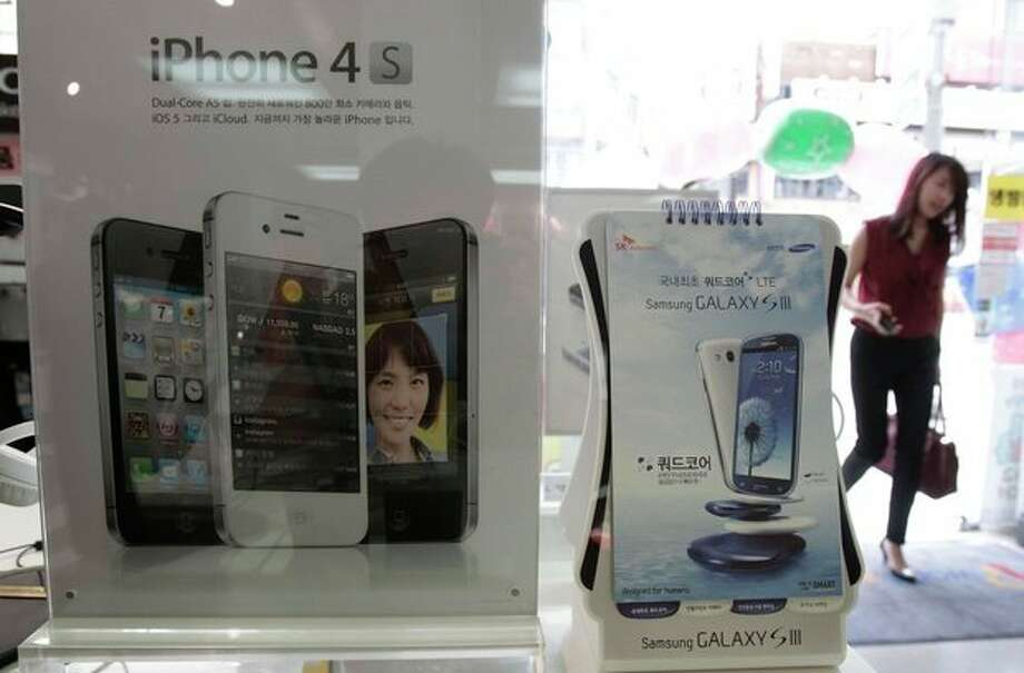 Banners advertising Samsung Electronics' Galaxy S III and Apple's iPhone 4S are displayed at a mobilephone shop in Seoul, South Korea, Monday, Aug. 27, 2012. After more than three weeks of trial in the U.S. and two days of deliberations, the nine-person jury said Friday that Samsung copied Apple's iPhone and iPad and ordered the South Korean firm to pay more than $1 billion in damages. (AP Photo/Ahn Young-joon) / AP