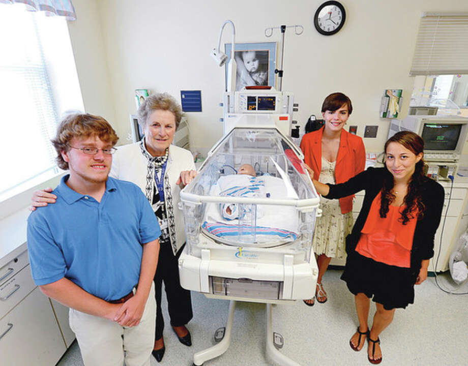 Hour photo / Erik TrautmannFrom left, Paul Orvis, Carole Bauer, Samantha Rutter and Sara Schafrann gather at Norwalk Hospital's Neonatal Intensive Care Unit. Bauer, chaplain of the NICU, said she was proud of the trio who were born premature, and grew up to volunteer to help with other preemies. / (C)2012, The Hour Newspapers, all rights reserved