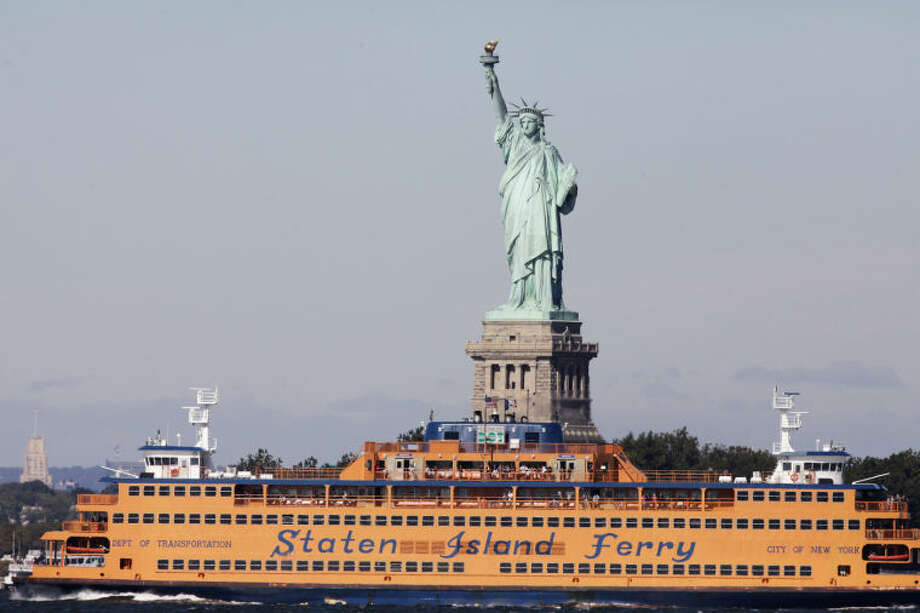 FILE - In this Oct. 1, 2012 file photo, the Staten Island Ferry passes the Statue of Liberty as it crosses New York Harbor. The Statue of Liberty, which has been closed to visitors since Superstorm Sandy, is scheduled to reopen for tours July Fourth, when Statue Cruises resumes departures for Liberty Island from Lower Manhattan. For tourists who want a photo of the famous statue without visiting the island, there are many options and vantage points, including rides on the free Staten Island Ferry. (AP Photo/Mark Lennihan, file)