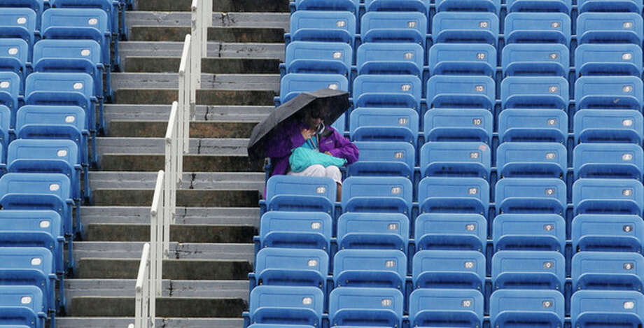 A fan uses an umbrella to keep dry during a rain delay at the 2012 US Open Tennis tournament, Monday, Aug. 27, 2012, in New York. (AP Photo/Mel C. Evans) / AP