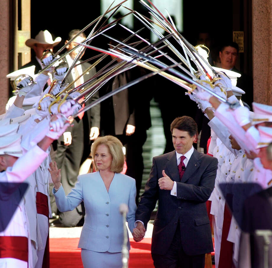 FILE - In this Jan. 21, 2003, file photo Texas Gov. Rick Perry, with his wife Anita, walks under the Ross Volunteers saber arch during Perry's inauguration in Austin, Texas. Perry announced Monday, July 8, 2013, that he would not seek re-election as Texas governor next year. (AP Photo/Eric Gay, File) / AP