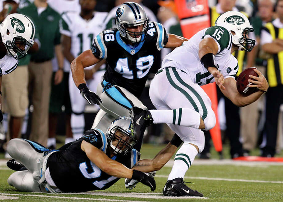 New York Jets quarterback Tim Tebow (15) avoids tackles from Carolina Panthers' Jordan Senn (57) and J.J. Finley (49) during the second half of a preseason NFL football game Sunday, Aug. 26, 2012, in East Rutherford, N.J. (AP Photo/Julio Cortez) / AP