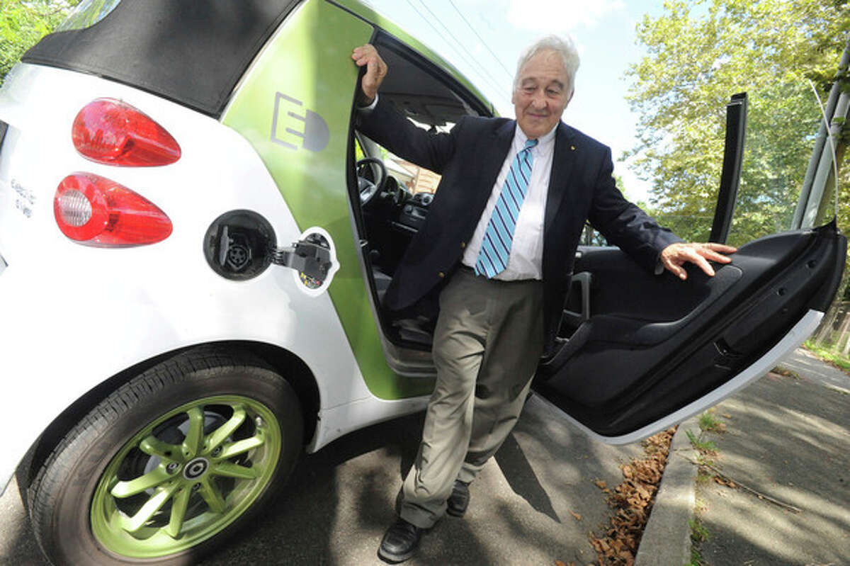 hour photo/matthew vinci Leo Cirino, technical consultant with the Town of Westport with a Smart Car by the Daimler company. Westport and CL&P unveiled the first electric vehicle charging station in 2012 at the Westport train station.