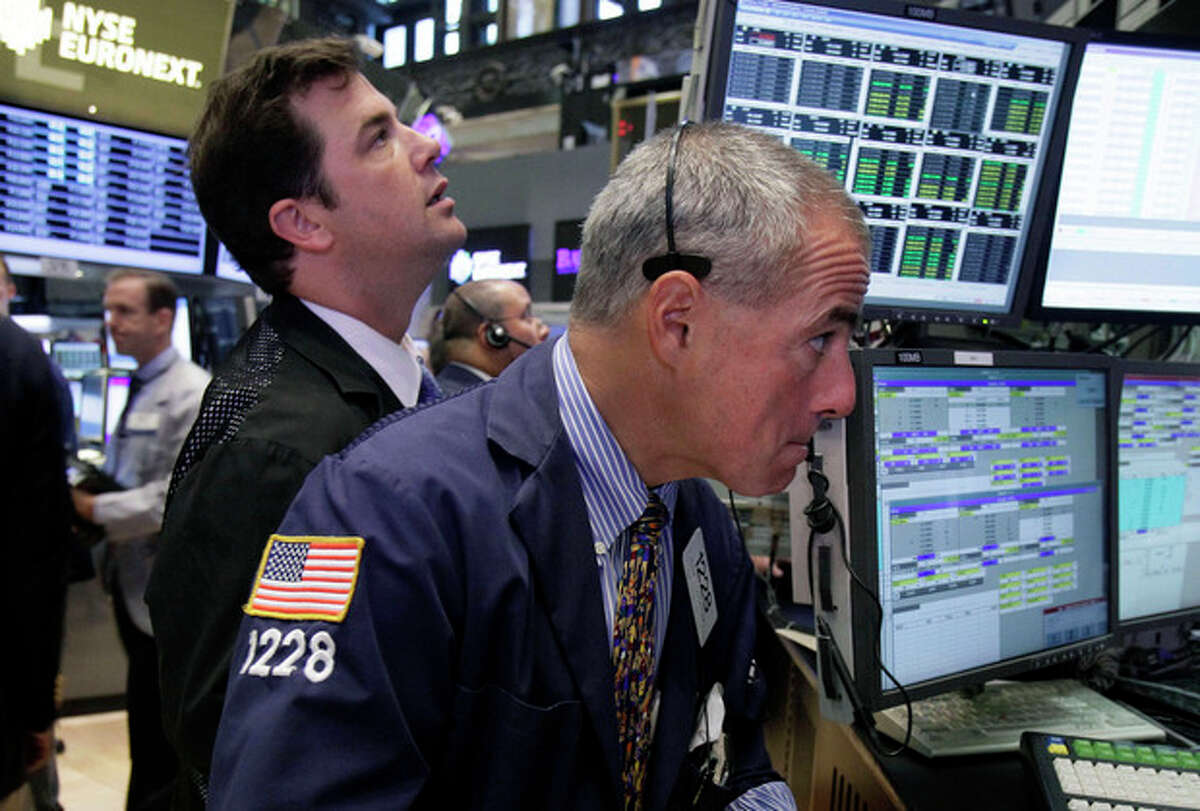 FILE- In a Wednesday, Aug. 15, 2012, file photo, Trader Frank Cannarozzo, right, works on the floor of the New York Stock Exchange. Trading volume, the number of shares bought and sold each day, is down by a fifth from last year, more evidence that relatively few investors are pushing up stocks as Main Street folks abandon the market.