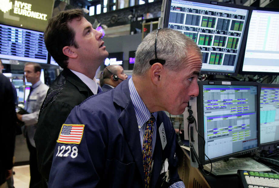 """FILE- In a Wednesday, Aug. 15, 2012, file photo, Trader Frank Cannarozzo, right, works on the floor of the New York Stock Exchange. Trading volume, the number of shares bought and sold each day, is down by a fifth from last year, more evidence that relatively few investors are pushing up stocks as Main Street folks abandon the market. """"August is usually slow, but this is terrible,"""" says Howard Silverblatt, senior index analyst at S&P Dow Jones Indices. (AP Photo/Richard Drew, File) / AP"""
