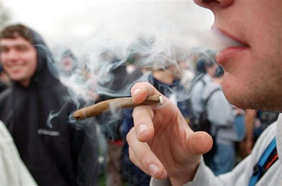 """FILE - In an April 20, 2005 file photo, a University of Colorado freshman, who did not want to be identified, joins a crowd smoking marijuana during a """"420"""" gathering at Farrand Field at the University of Colorado in Boulder, Colo. People who started using marijuana persistently before age 18 risk losing some of their IQ by the time they're 38, a long-running study says. In contrast, even long-term chronic users who started after age 18 showed no such effect, suggesting the drug holds some particular toxicity for the developing brain. (AP Photo/Longmont Daily Times-Call, Richard M. Hackett, File) MANDATORY CREDIT, MAGS OUT, NO SALES / LONGMONT DAILY TIMES-CALL"""