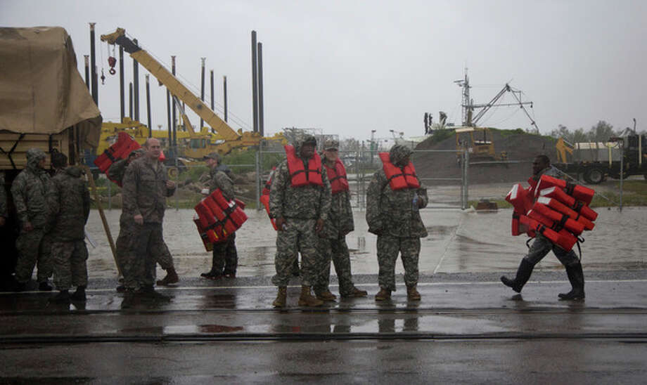 Guardsmen distribute life vests near Braithwaite, La., as they prepare to help flood victims from Plaquemines Parish, a rural area outside New Orleans that was flooded during Hurricane Isaac on Wednesday, Aug. 29, 2012. (AP Photo/Erik Schelzig) / AP