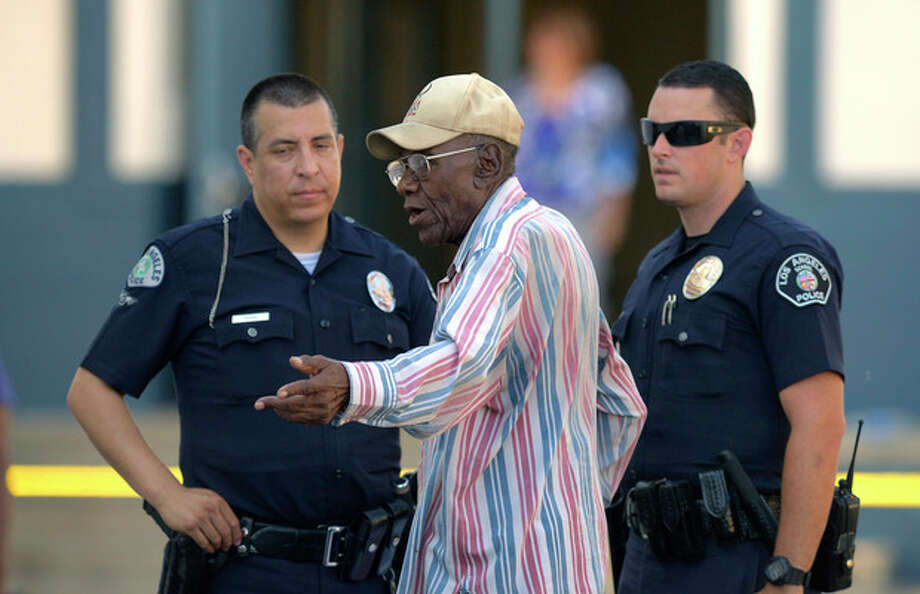 Preston Carter, 100, talks with police officers after police say his car went onto a sidewalk and plowed into a group of parents and children outside a South Los Angeles elementary school, Wednesday, Aug. 29, 2012, in Los Angeles. Nine children and two adults were injured in the wreck. (AP Photo/Mark J. Terrill) / AP