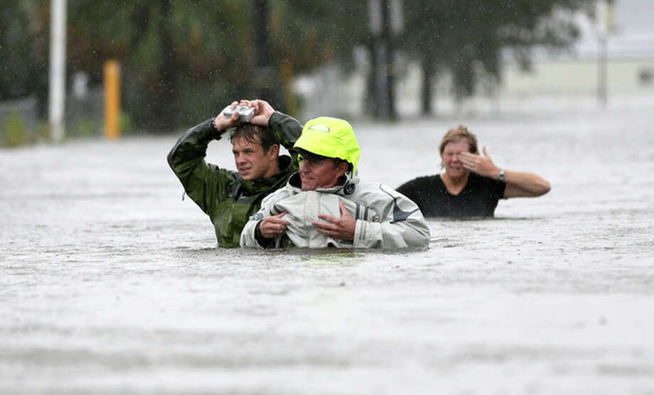 Chuck Cropp, center, his son Piers, left, and wife Liz, right, wade through floodwaters from Hurricane Isaac Wednesday, Aug. 29, 2012, in New Orleans. As Isaac made landfall, it was expected to dump as much as 20 inches of rain in several parts of Louisiana. (AP Photo/David J. Phillip) / AP