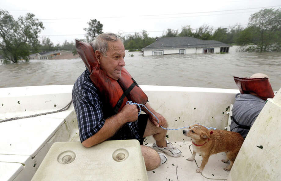 Carlo Maltese and his dog Pin ride in a boat after being rescued from his flooded home as Hurricane Isaac hits Wednesday, Aug. 29, 2012, in Braithwaite, La. (AP Photo/David J. Phillip) / AP