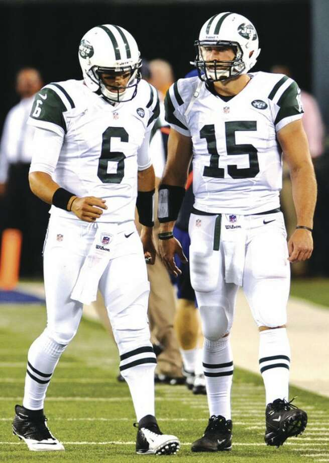 AP photoNew York Jets quarterbacks Mark Sanchez, left, and Tim Tebow meet near the sidelines after Sanchez threw an interception during an August preseason game. The presence of the two contrasting QBs on the roster has overshadowed everything else at the team's training camp.