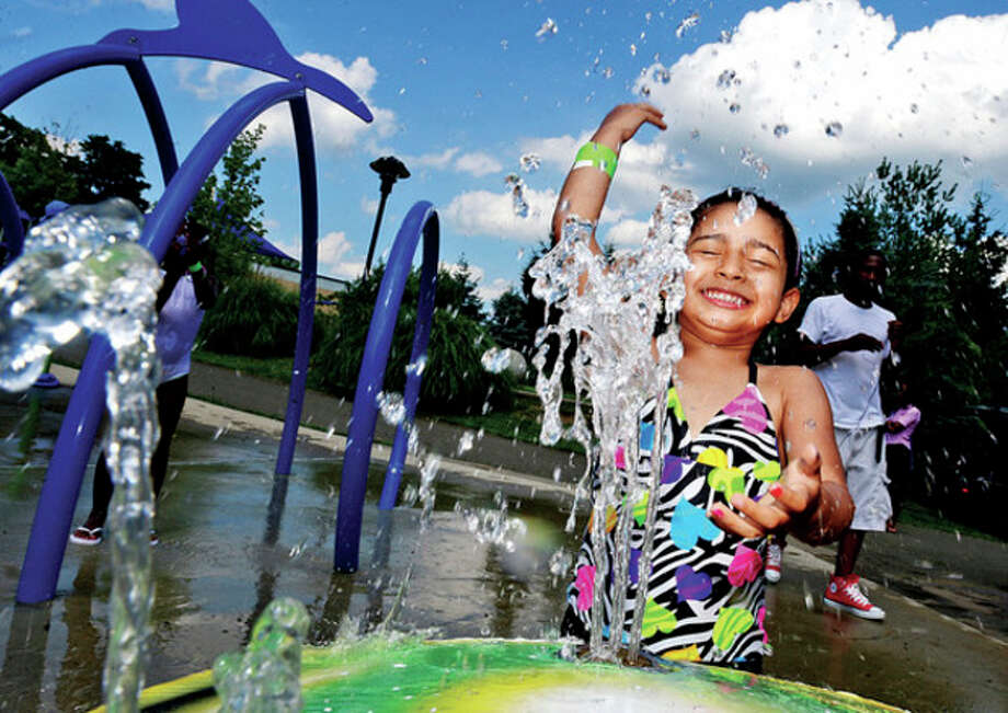 Hour photo / Erik TrautmannA cool splashHelen Veliz, 4, cools off on the splash pad in Devon's Place playground at Mathews Park Saturday as temperatures reached into the 90's. / (C)2013, The Hour Newspapers, all rights reserved