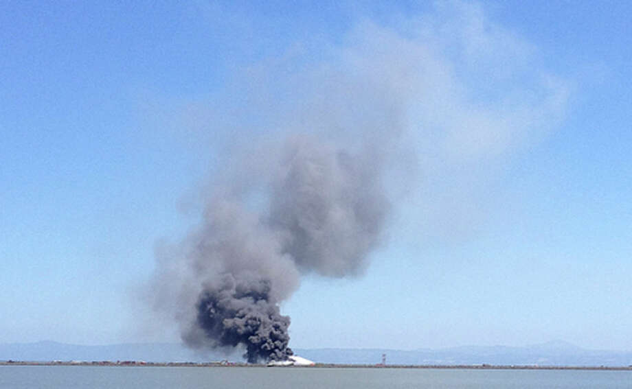 In this photo provided by Scott Sobczak, smoke rises from of Asiana Flight 214 after it crashed at San Francisco International Airport in San Francisco, Saturday, July 6, 2013. (AP Photo/Scott Sobczak) MANDATORY CREDIT / Scott Sobczak