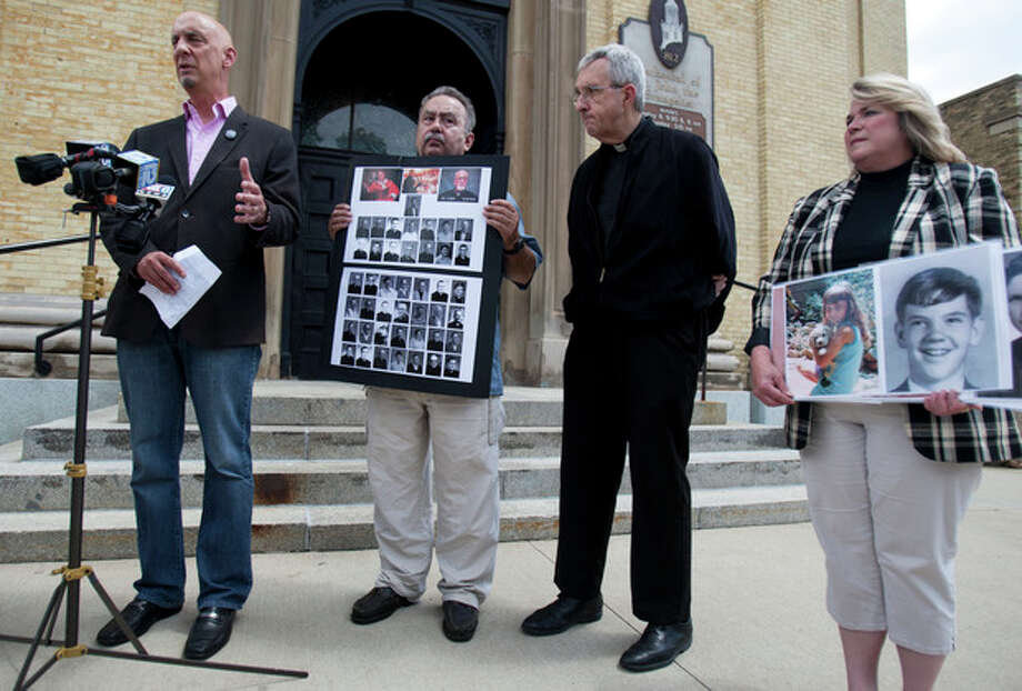 In this June 28, 2013 photo, from left, Peter Isely, Arthur Budzinski, Fr. James Connell and Monica Barrett talk about the importance of the release of priest abuse files by the Archdiocese of Milwaukee on the front stairs of St. John's Cathedral in Milwaukee. Clergy sex abuse victims have long accused the Archdiocese of Milwaukee of spending more money on lawyers to protect itself than to care for those who suffered at the hands of abusive priests. An Associated Press analysis of documents released tMonday, July 1 found most of the $30 million the archdiocese paid out through mid-2012 went to victim settlements and therapy, but the bulk of it went to just a few victims _ while hundreds of others got no money at all. They include Barrett, who said she was raped in a church at age 8 by William Effinger. She sued the archdiocese in 1993, when she was 32, but a judge dismissed her case, saying too much time had passed. She appealed, but got nowhere. Meanwhile, the archdiocese sued her for $14,000 to cover its legal costs. (AP Photo/Milwaukee Journal Sentinel, Mark Felix) / Milwaukee Journal Sentinel