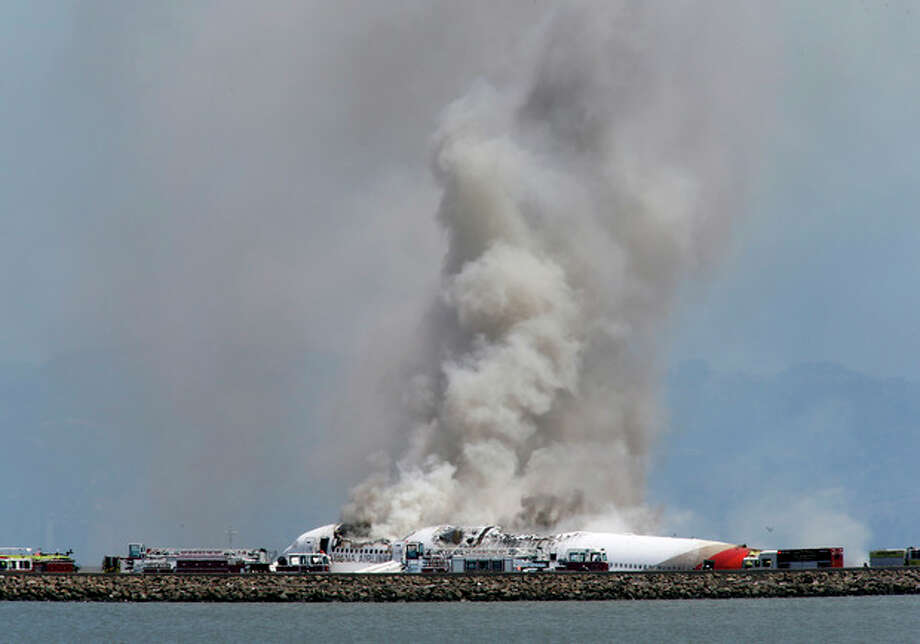 Smokes rises from Asiana Flight 214 after it crashed at San Francisco International Airport in San Francisco, Saturday, July 6, 2013. (AP Photo/Bay Area News Group, John Green) / San Jose Mercury News