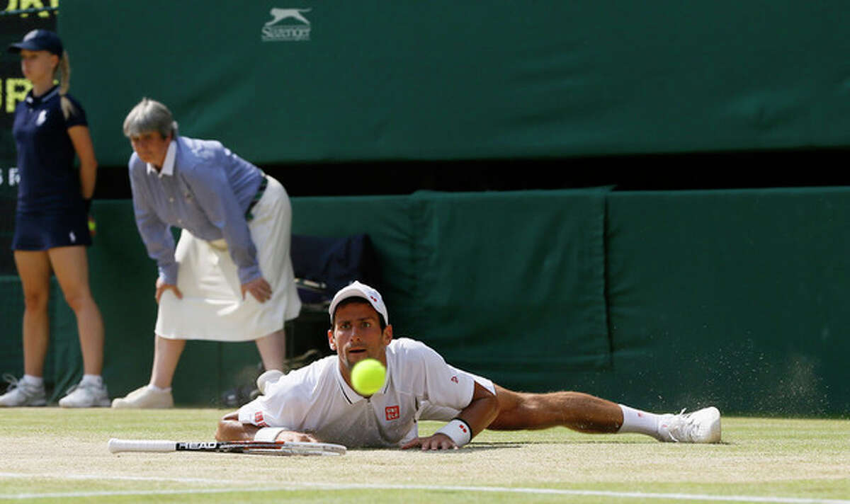 Novak Djokovic of Serbia looks at the ball after slipping as he plays Andy Murray of Britain during the Men's singles final match at the All England Lawn Tennis Championships in Wimbledon, London, Sunday, July 7, 2013.(AP Photo/Kirsty Wigglesworth)