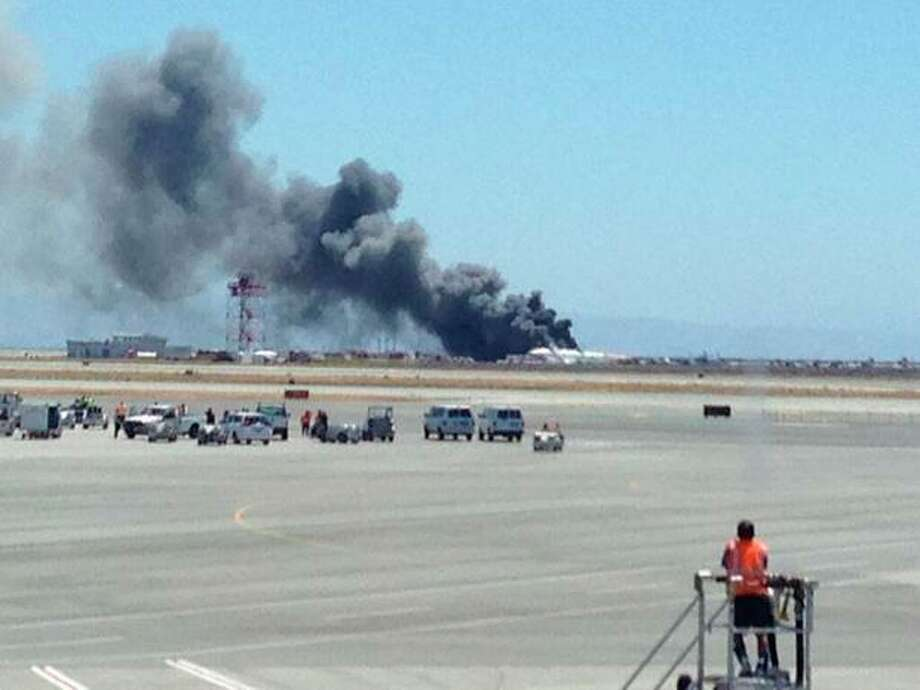 This photo provided by Krista Seiden shows smoke rising from what a federal aviation official says was an Asiana Airlines flight crashing while landing at San Francisco airport on Saturday, July 6, 2013. (AP Photo/Krista Seiden) / AP