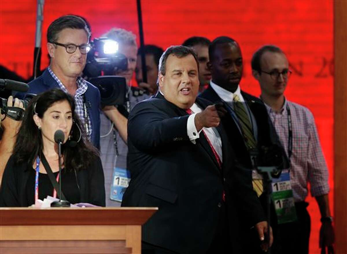 New Jersey Governor Chris Christie, right, stands on the main stage in the Tampa Tribune Forum before the start of the Republican National Convention in Tampa, Fla., on Monday, Aug. 27, 2012. (AP Photo/J. Scott Applewhite)