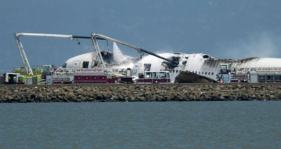 A fire truck sprays water on Asiana Flight 214 after it crashed at San Francisco International Airport on Saturday, July 6, 2013, in San Francisco. (AP Photo/Noah Berger) / FR34727 AP