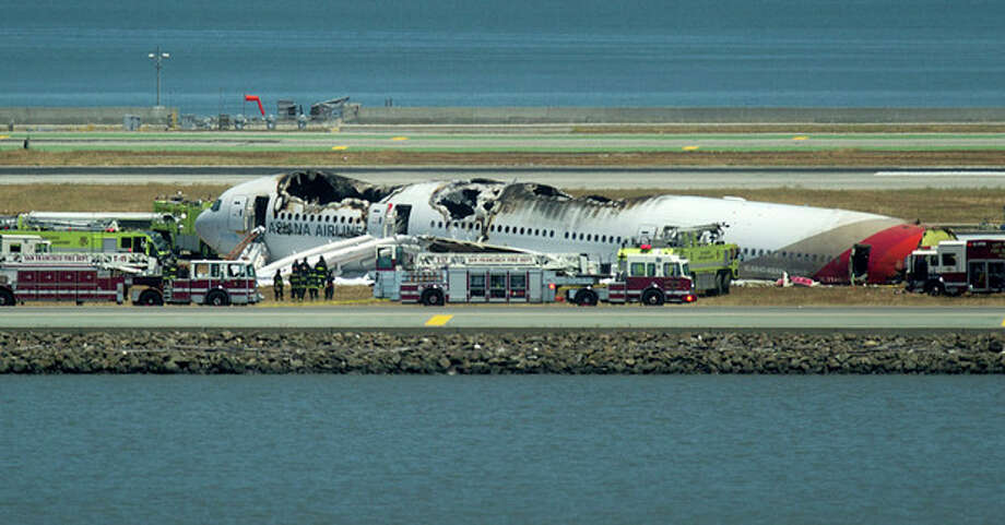 Fire crews respond to the scene where Asiana Flight 214 crashed at San Francisco International Airport on Saturday, July 6, 2013, in San Francisco. (AP Photo/Noah Berger) / FR34727 AP