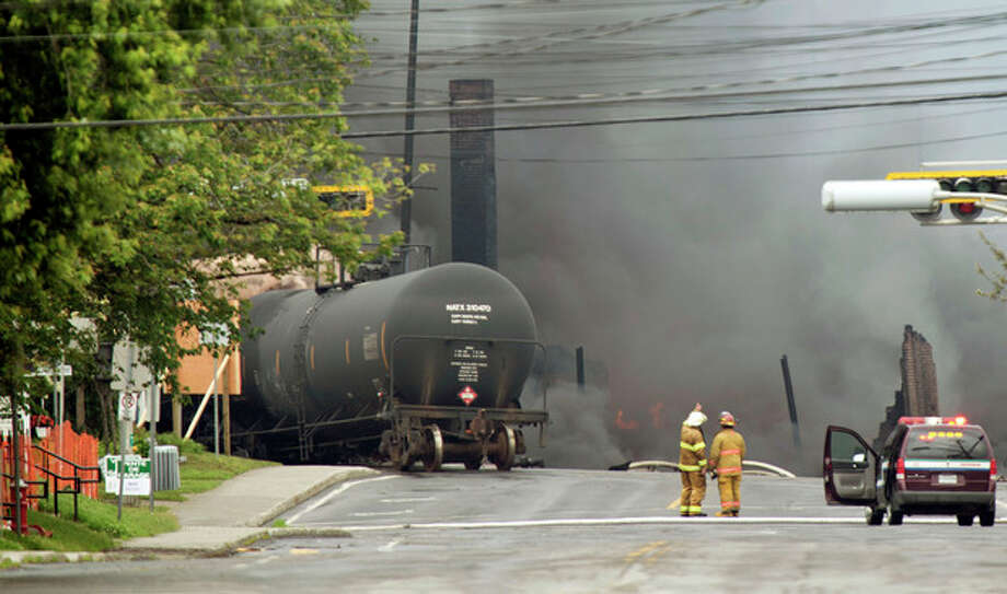 Smoke rises from railway cars that were carrying crude oil after derailing in downtown Lac Megantic, Quebec, Canada, Saturday, July 6, 2013. The derailment sparked several explosions and forced the evacuation of up to 1,000 people. (AP Photo/The Canadian Press, Paul Chiasson) / The Canadian Press