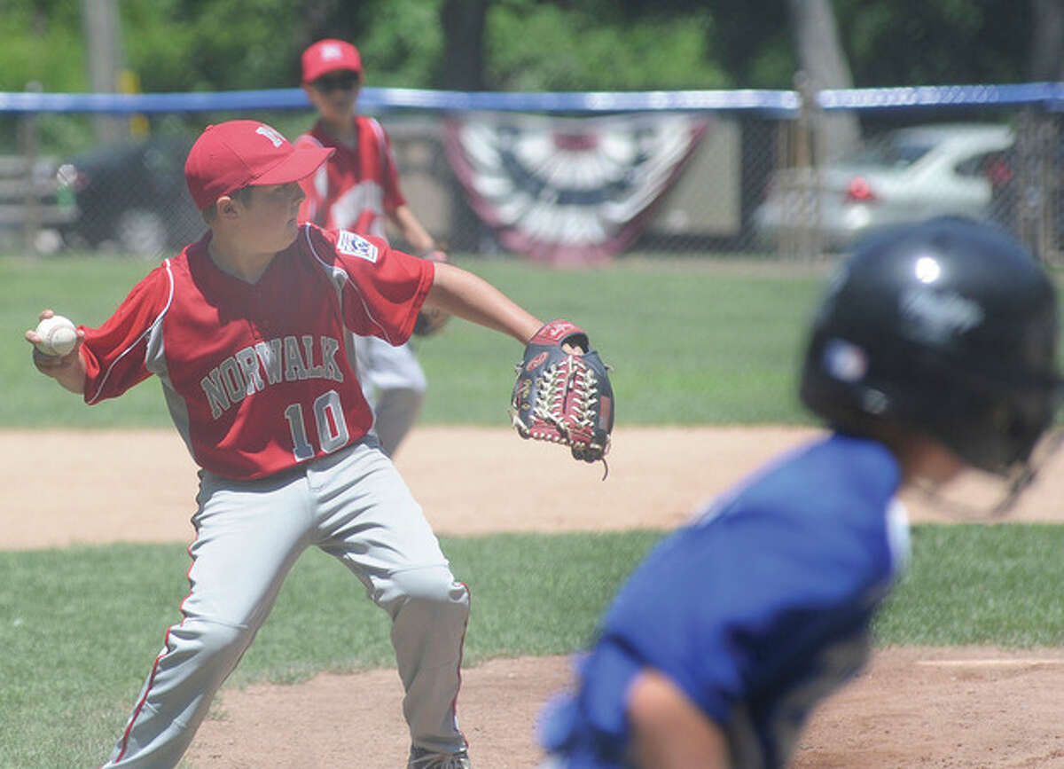 Hour photo/Matthew Vinci Norwalk pitcher Cooper Grillo, left, throws out Darien's Thomas Ostberg on a comebacker to the mound during Sunday's 10-year-old quarterfinal.