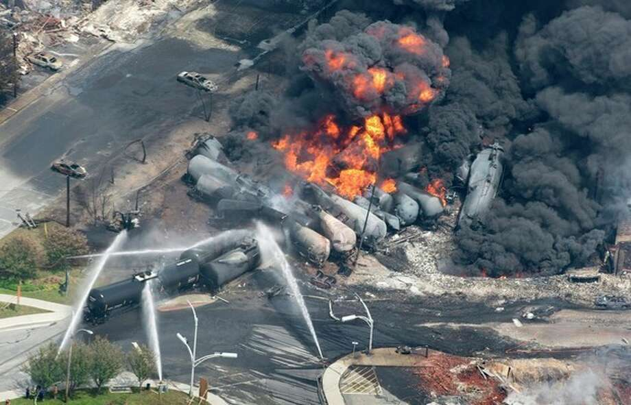 Smoke rises from railway cars that were carrying crude oil after derailing in downtown Lac Megantic, Quebec, Canada, Saturday, July 6, 2013. A large swath of Lac Megantic was destroyed Saturday after a train carrying crude oil derailed, sparking several explosions and forcing the evacuation of up to 1,000 people. (AP Photo/The Canadian Press, Paul Chiasson) / The Canadian Press