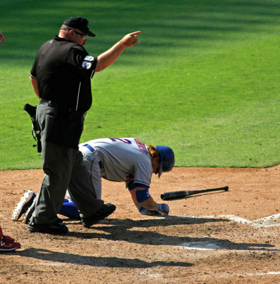 Home plate umpire Wally Bell singles to first after New York Mets' Justin Turner was hit by a pitch in the ninth inning of a baseball game against the Philadelphia Phillies, Thursday, Aug. 30, 2012, in Philadelphia. The Phillies won 3-2. (AP Photo/H. Rumph Jr) / FR61717 AP