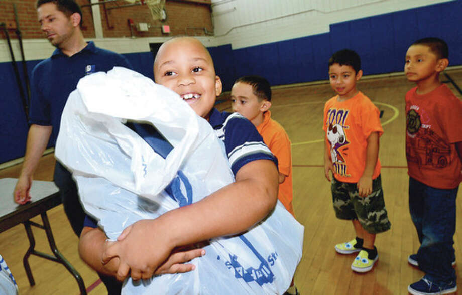 Goodwill donates over 500 backpacks to Kendall Elementary School students including 2nd grader Alvan Lubin Thursday.Hour photo / Erik Trautmann / (C)2012, The Hour Newspapers, all rights reserved
