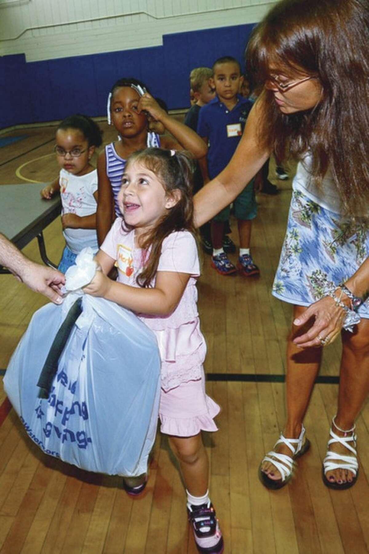 Goodwill donates over 500 backpacks to Kendall Elementary School students including kindergartner Merly Enriquez Thursday. Hour photo / Erik Trautmann