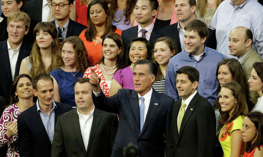 Republican presidential nominee Mitt Romney points to the photographer as he and vice presidential nominee, Rep. Paul Ryan, right, pose for a group photo with campaign staff before the Republican National Convention in Tampa, Fla., on Thursday, Aug. 30, 2012. (AP Photo/Lynne Sladky) / AP