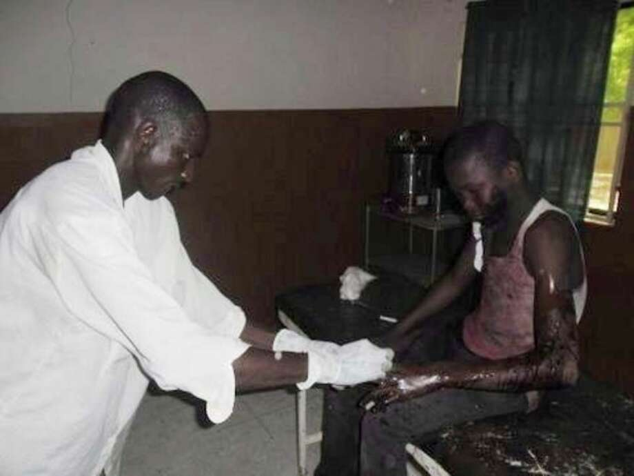 In this photo taken with a mobile phone a doctor attends to a student from Government Secondary School in Mamudo, at the Potiskum General Hospital, Nigeria, following an attack by gunmen on Saturday July 6, 2013. Islamic militants attacked a boarding school before dawn Saturday, dousing a dormitory in fuel and lighting it ablaze as students slept, survivors said. At least 30 people were killed in the deadliest attack yet on schools in Nigeria's embattled northeast. (AP Photo/Adamu Adamu) / AP