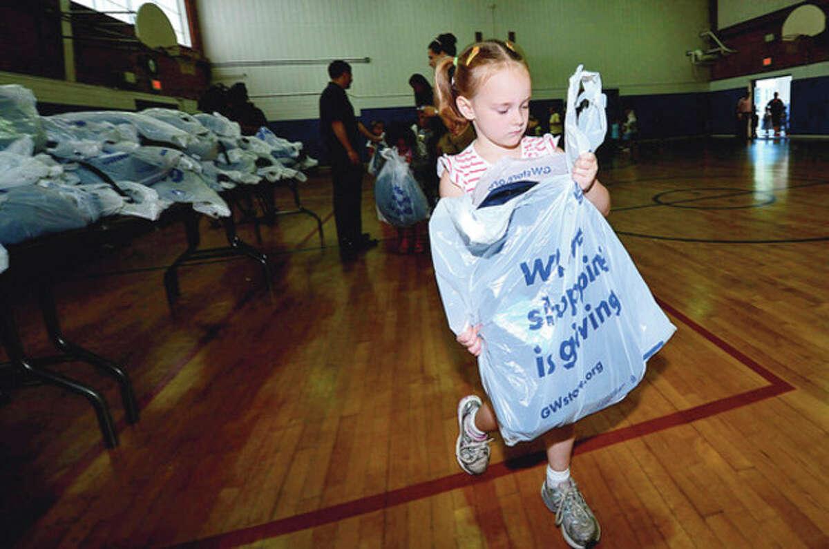 Goodwill donates over 500 backpacks to Kendall Elementary School students including kindergartner Erica Horowitz Thursday. Hour photo / Erik Trautmann