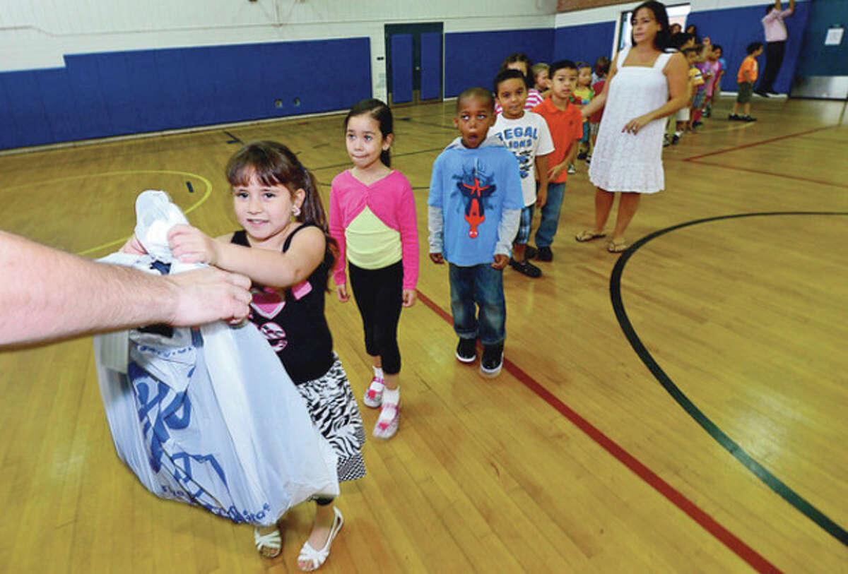 Goodwill donates over 500 backpacks to Kendall Elementary School students including kindergartner Daly Avalos Thursday. Hour photo / Erik Trautmann