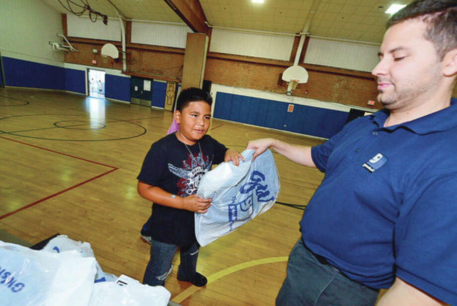 Goodwill donates over 500 backpacks to Kendall Elementary School students including 5th grader Sebastian Ventura Thursday.Hour photo / Erik Trautmann / (C)2012, The Hour Newspapers, all rights reserved