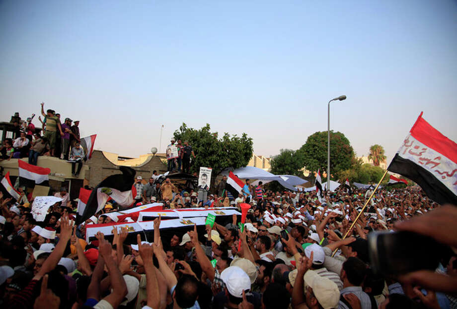 Supporters of Egypt's ousted President Mohammed Morsi carry coffins, covered with the national flag, of four men killed after Egyptian troops opened fire on mostly Islamist protesters marching on a Republican Guard headquarters Friday, in Cairo, Saturday, July 6, 2013. (AP Photo/Khalil Hamra) / AP
