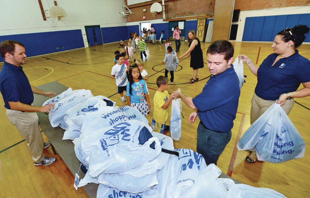Goodwill workers, Thomas Lintern, Frank Losqudro and Ashley Telesco, donate over 500 backpacks to Kendall Elementary School students Thursday. Hour photo / Erik Trautmann