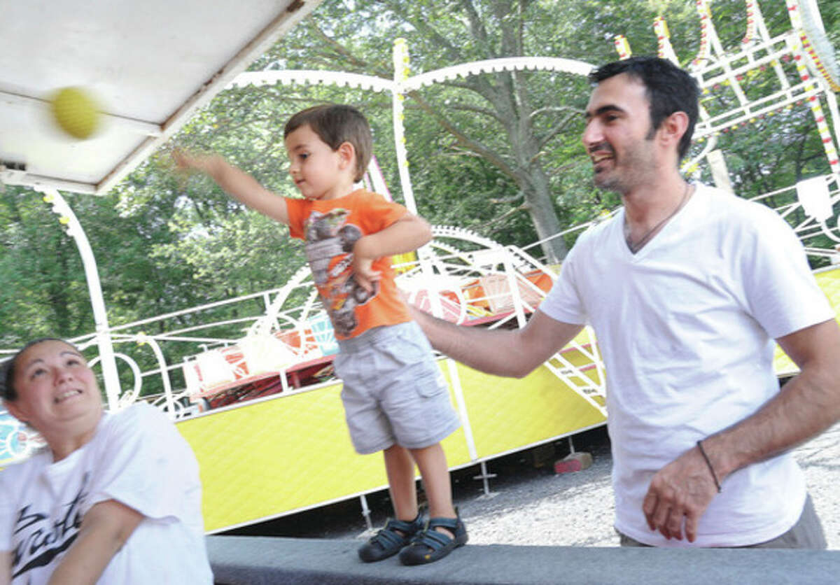 George Konstantinidis with his 2 year old son Ilias enjoy the games at the Greek Festival at the St. George Greek Orthodox Church on Sunday. hour photo/Matthew Vinci