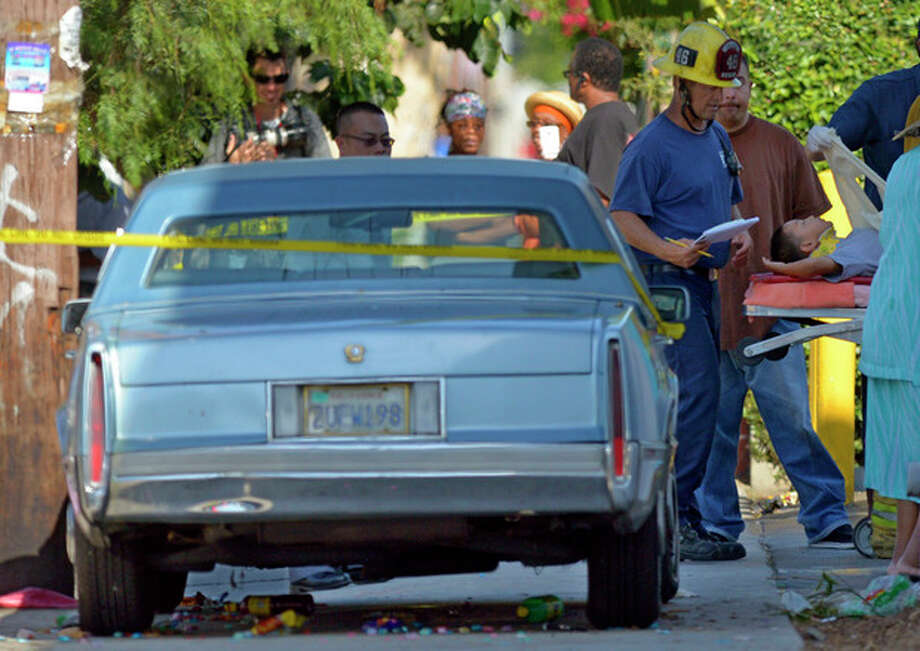 A young victim is treated by Los Angeles city firefighters after a car driven by a 100-year-old went onto a sidewalk and plowed into a group of parents and children outside a South Los Angeles elementary school, Wednesday, Aug. 29, 2012, in Los Angeles. Nine children and two adults were injured in the wreck. (AP Photo/Mark J. Terrill) / AP