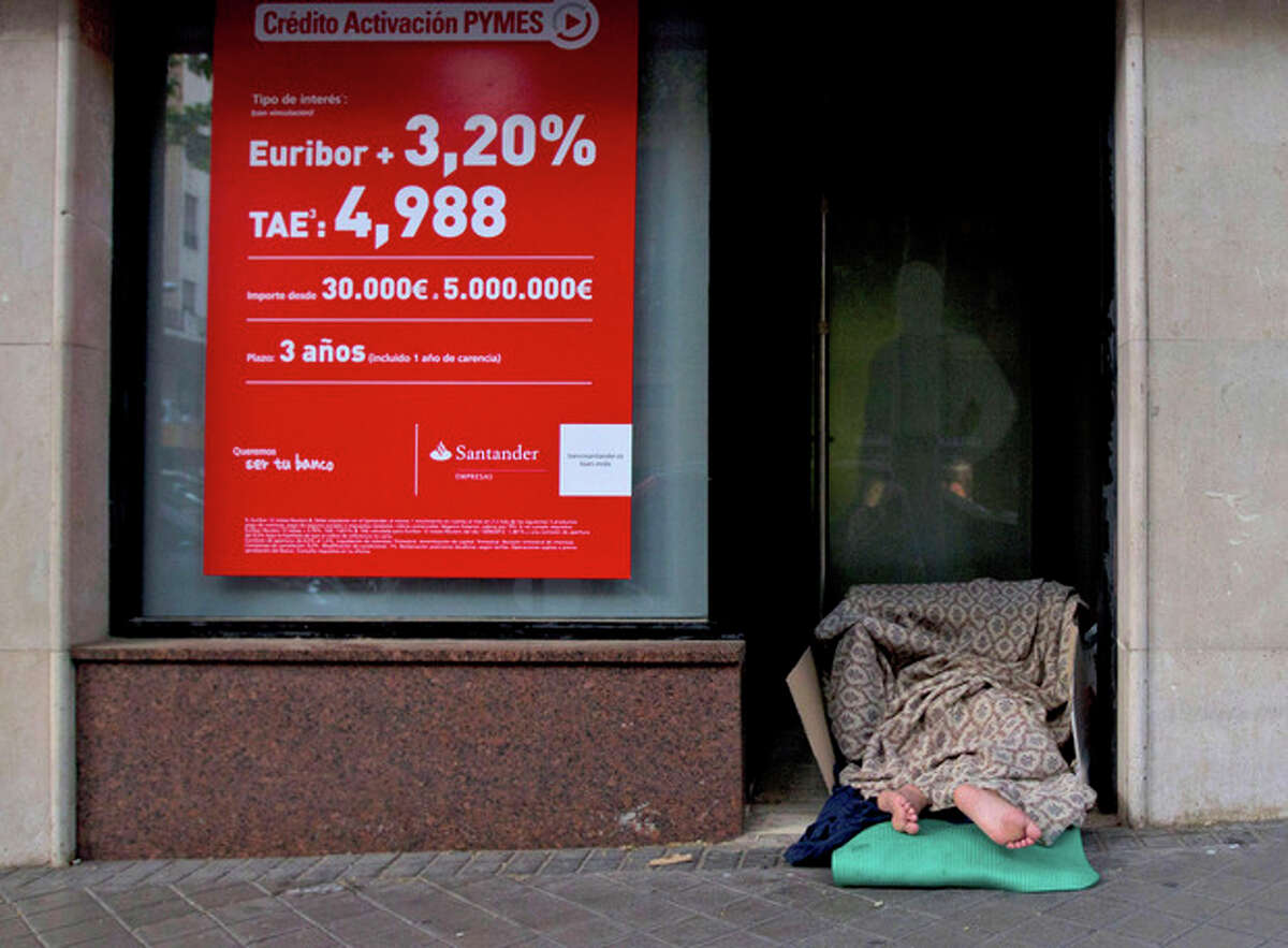 FILE - In this June 7, 2012 file photo, a homeless person sleeps in the doorway of a bank in Madrid. The Spanish government on Friday Aug. 31, 2012 is expected to approve a law setting up a 'bad bank' that will pool many of the property-related toxic assets held by its ailing banks. The Cabinet may also approve a decree giving its central bank more power to intervene faster in banks deemed to be shaky. (AP Photo/Paul White, File)