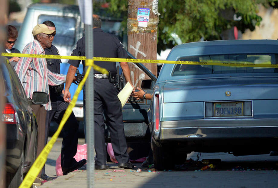 Preston Carter, left, 100, talks with police officers after police say his car went onto a sidewalk and plowed into a group of parents and children outside a South Los Angeles elementary school, Wednesday, Aug. 29, 2012, in Los Angeles. Nine children and two adults were injured in the wreck. (AP Photo/Mark J. Terrill) / AP