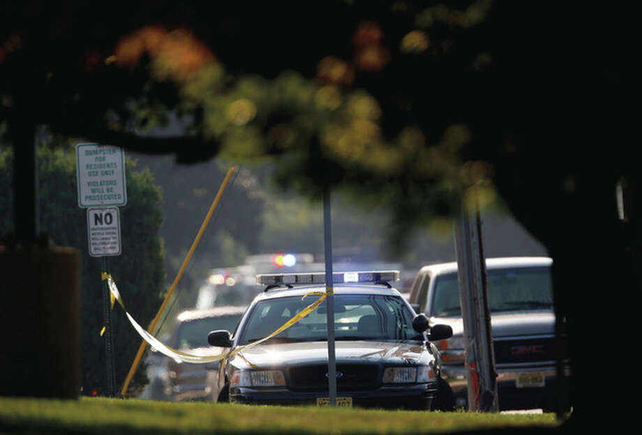 Officials investigate the scene of a shooting at a Pathmark grocery store in Old Bridge, N.J., Friday, Aug. 31, 2012. At least three people have died in the shooting. A law enforcement official briefed on the shooting says the person believed to be the shooter is among the dead. (AP Photo/Julio Cortez) / AP